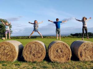 Kids on top fo round bales, jumping into the air.