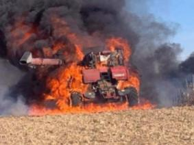 Picture of a combine on fire in a field.
